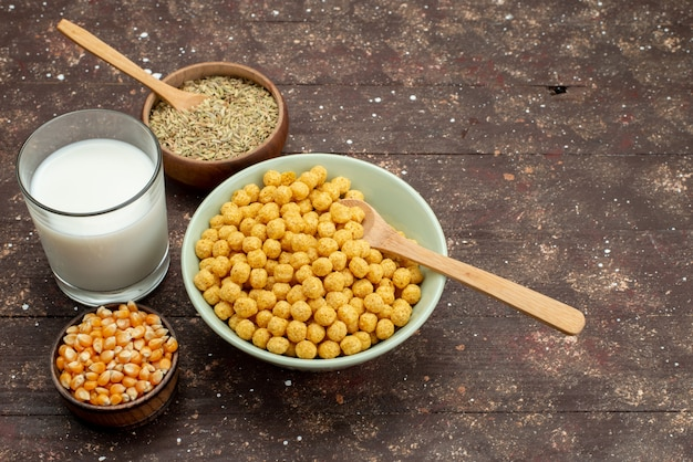 Vue avant des céréales jaunes à l'intérieur de la plaque avec du lait froid frais sur bois foncé, petit-déjeuner céréales céréales cornflakes