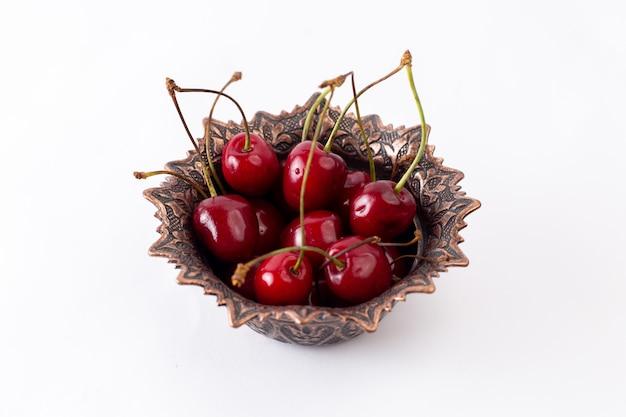 Vue avant des cerises aigres rouges à l'intérieur de la plaque sur le jus de fruits blancs moelleux