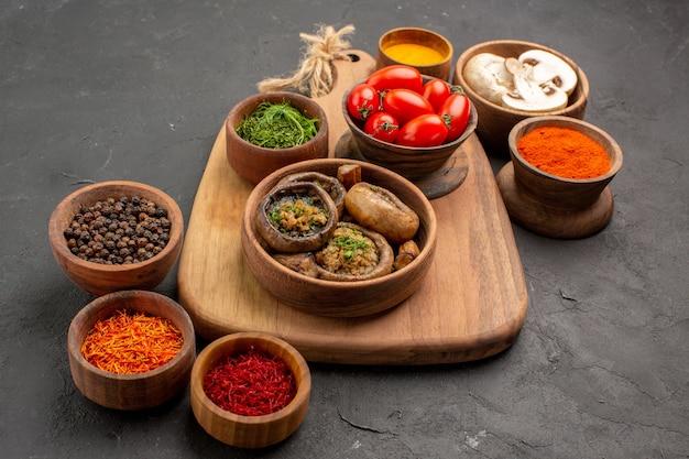 Vue avant de champignons cuits avec assaisonnements sur table gris foncé champignon alimentaire mûr