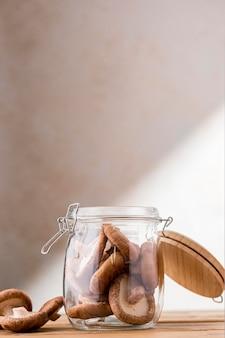 Vue avant des champignons dans un bocal en verre avec espace copie