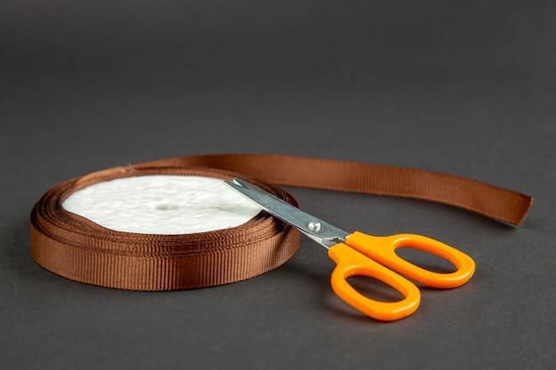 Vue avant des ciseaux orange avec un arc sur la surface sombre de l'obscurité de la couture de la broche mesure couleur photo