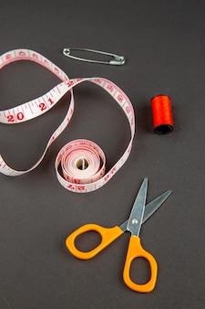 Vue avant des ciseaux orange avec des centimètres sur une surface sombre photo obscurité vêtements broche couleur travail mesure couture