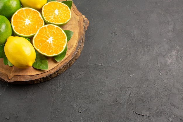 Vue avant des citrons aigres frais sur plancher sombre arbre citron vert fruits agrumes
