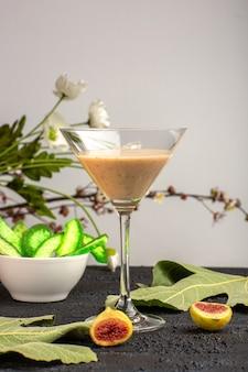 Vue avant des cocktails frais avec des fleurs et des figues sur une surface violette