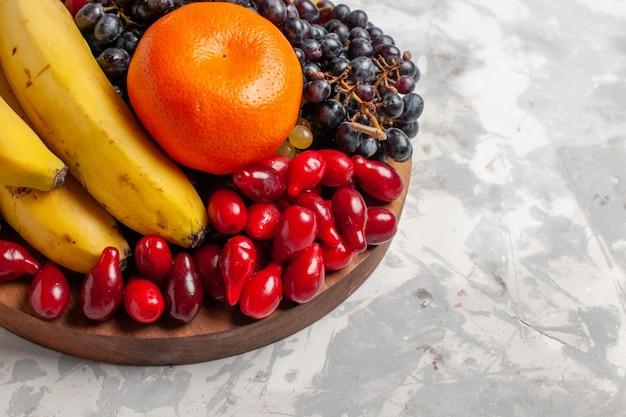 Vue avant de la composition des fruits bananes cornouiller et raisins sur surface blanche fruits baies fraîcheur vitamine