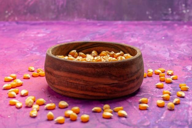 Vue avant des cors bruts à l'intérieur de la plaque sur le maïs soufflé de couleur maïs table rose
