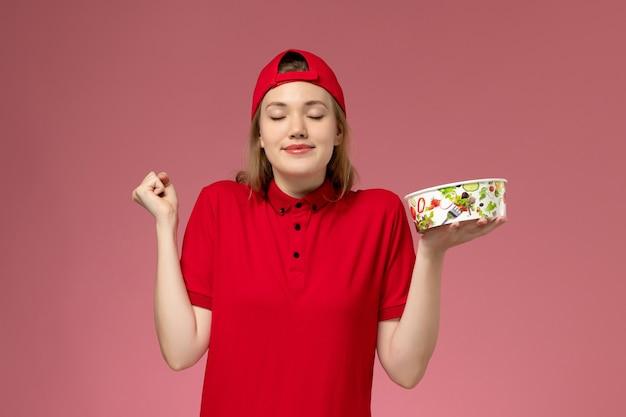 Vue avant de courrier féminin en uniforme rouge et cape tenant le bol de livraison sur le mur rose clair, la livraison d'uniforme de service d'emploi des travailleurs