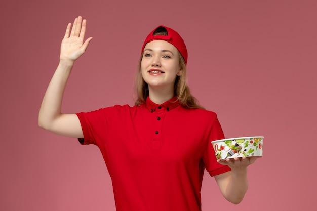 Vue avant de courrier féminin en uniforme rouge et cape tenant le bol de livraison sur le mur rose clair, la livraison d'uniforme de service de fille d'emploi de travailleur
