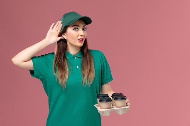 Vue avant de courrier féminin en uniforme vert et cape tenant des tasses de café de livraison tryign d'entendre sur le mur rose service de livraison uniforme