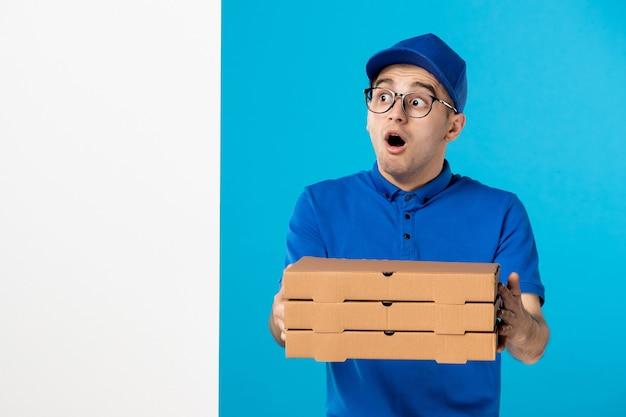 Vue avant de courrier masculin avec des boîtes de pizza de livraison sur bleu
