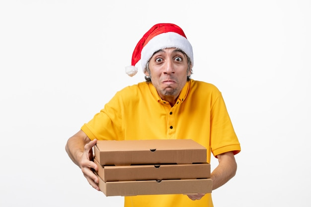 Vue avant de courrier masculin avec des boîtes de pizza sur un mur blanc de travail de service de nouvel an uniforme