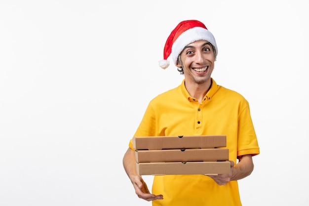 Vue avant de courrier masculin avec des boîtes de pizza sur le service de livraison d'emploi uniforme de mur blanc