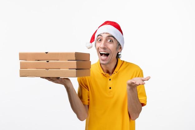 Vue avant de courrier masculin avec des boîtes de pizza sur le service de livraison uniforme de mur blanc