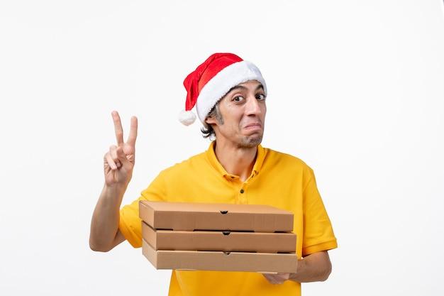 Vue avant de courrier masculin avec des boîtes de pizza sur un travail uniforme de service de mur blanc