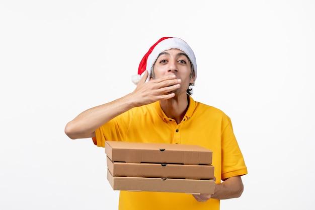 Vue avant de courrier masculin avec des boîtes de pizza sur l'uniforme de livraison de service de travail de mur blanc