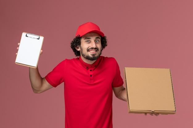 Vue avant de courrier masculin en chemise rouge et cape tenant la boîte de nourriture de livraison et le bloc-notes sur le mur rose