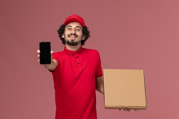 Vue avant de courrier masculin en chemise rouge et cape tenant la boîte de nourriture de livraison vide avec téléphone sur mur rose