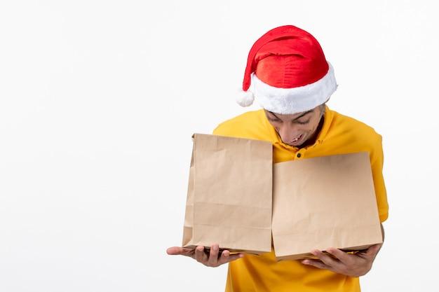 Vue avant de courrier masculin avec des colis de nourriture sur le sol blanc travail de service uniforme de repas
