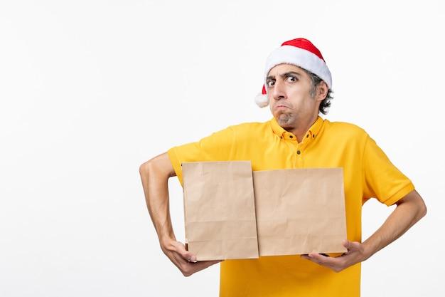 Vue avant de courrier masculin avec des paquets de nourriture sur le sol blanc service uniforme de travail de repas