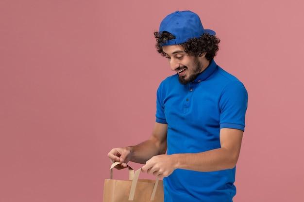 Vue avant de courrier masculin en uniforme bleu et cape tenant le paquet de nourriture de papier de livraison sur le mur rose service de livraison travailleur uniforme