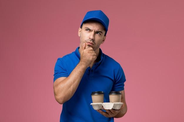 Vue avant de courrier masculin en uniforme bleu avec expression de pensée tenant le café sur le mur rose, travailleur de la prestation de services uniforme de travail