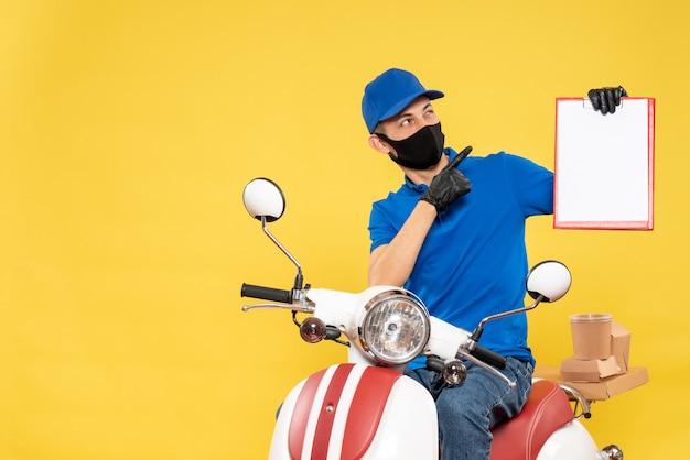 Vue avant de courrier masculin en uniforme bleu avec note de fichier sur le travail de vélo jaune covid- service de livraison d'emploi