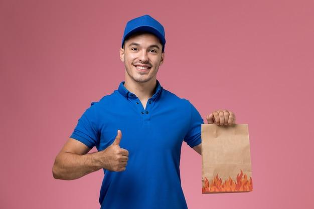 Vue avant de courrier masculin en uniforme bleu tenant un paquet de papier alimentaire avec le sourire sur le mur rose, la livraison d'un emploi de service uniforme