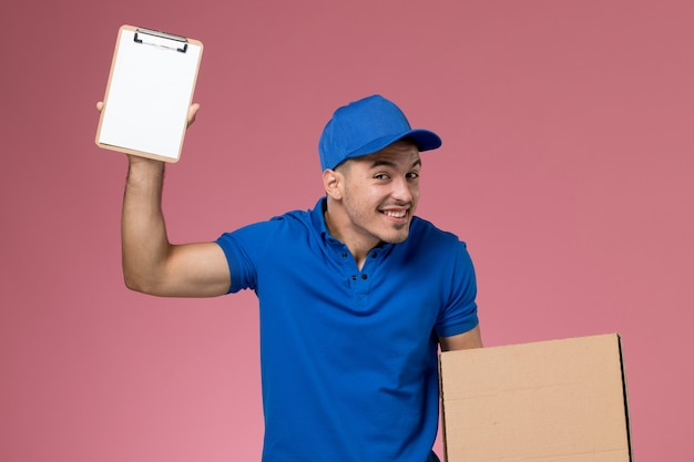 Vue avant de courrier masculin en uniforme bleu tenant petit bloc-notes et boîte de nourriture sur le mur rose, la prestation de services uniforme des travailleurs