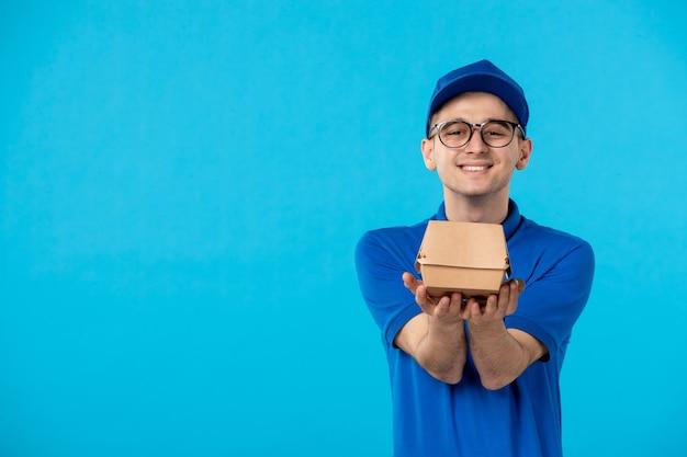 Vue avant de courrier masculin en uniforme avec colis de livraison sur un bleu