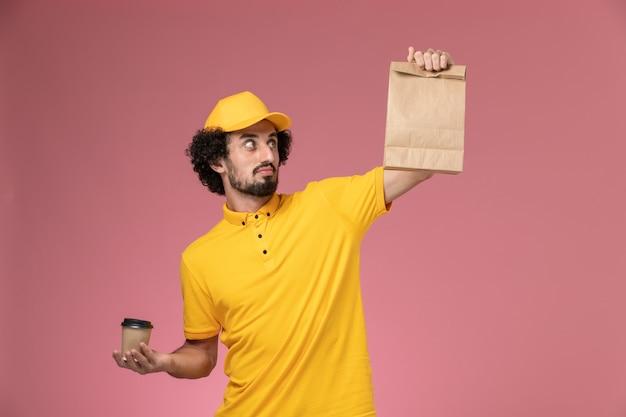 Vue avant de courrier masculin en uniforme jaune et cape tenant la tasse de café de livraison et le paquet de nourriture sur le bureau rose uniforme de travail de l'entreprise de service d'emploi