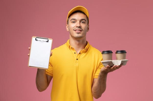 Vue avant de courrier masculin en uniforme jaune tenant le bloc-notes et la livraison des tasses de café sur fond rose