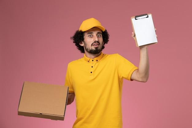 Vue avant de courrier masculin en uniforme jaune tenant la boîte de livraison de nourriture et le bloc-notes sur mur rose clair