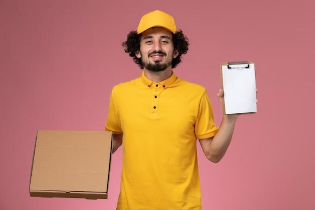 Vue avant de courrier masculin en uniforme jaune tenant la boîte de livraison de nourriture et le bloc-notes sur le mur rose