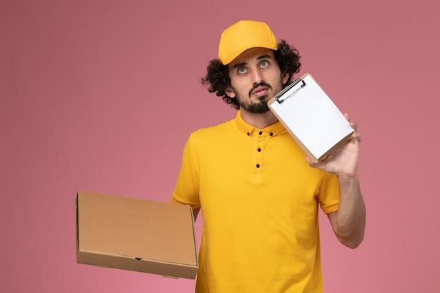 Vue avant de courrier masculin en uniforme jaune tenant la boîte de livraison de nourriture et le bloc-notes de réflexion profonde sur le mur rose