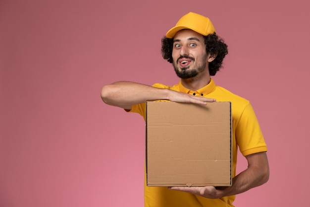 Vue avant de courrier masculin en uniforme jaune tenant la boîte de livraison de nourriture sur le mur rose clair