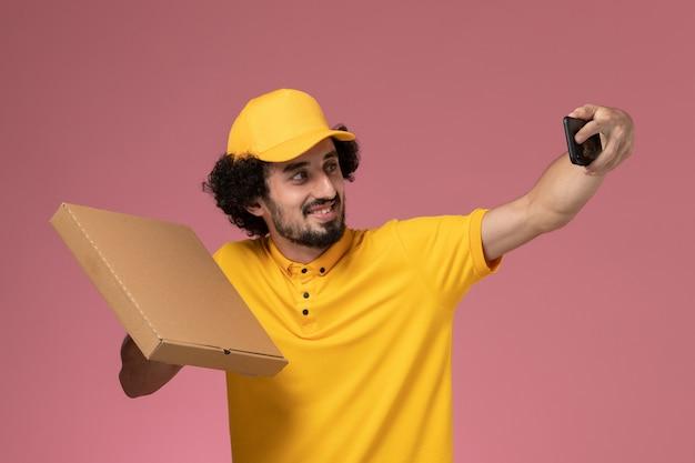 Vue avant de courrier masculin en uniforme jaune tenant la boîte de livraison de nourriture prenant photo sur mur rose