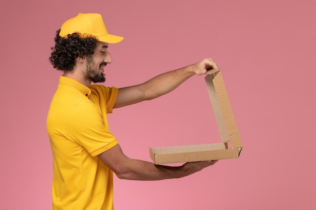 Vue avant de courrier masculin en uniforme jaune tenant une boîte de nourriture sur un mur rose clair