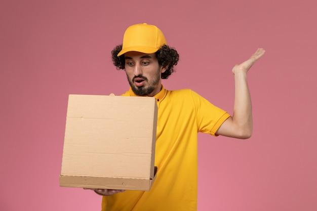Vue avant de courrier masculin en uniforme jaune tenant et ouvrant la boîte de livraison de nourriture sur le mur rose clair