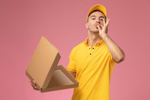 Vue avant de courrier masculin en uniforme jaune tenant et ouvrant la boîte de livraison de nourriture vide sur le bureau lightpink