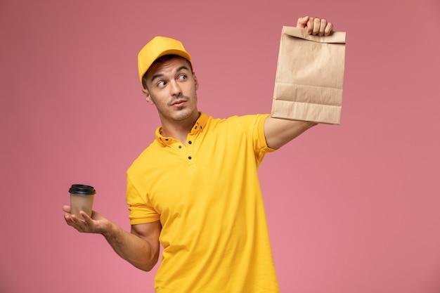 Vue avant de courrier masculin en uniforme jaune tenant la tasse de café de livraison et le paquet de nourriture sur le bureau rose clair