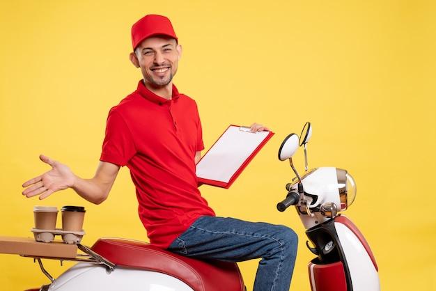 Vue avant de courrier masculin en uniforme rouge avec note de fichier sur la livraison de couleur jaune vélo travail uniforme de travail de service des travailleurs