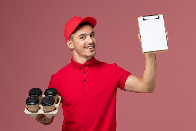 Vue avant de courrier masculin en uniforme rouge tenant des tasses de café de livraison avec bloc-notes sourire sur mur rose