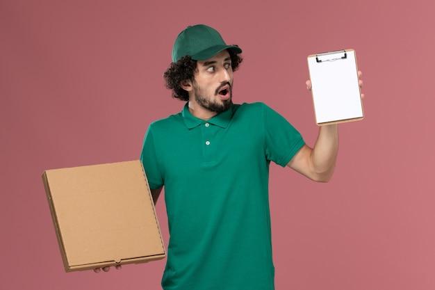 Vue avant de courrier masculin en uniforme vert et cape tenant le bloc-notes de boîte de nourriture de livraison sur le travail de livraison uniforme de service fond rose