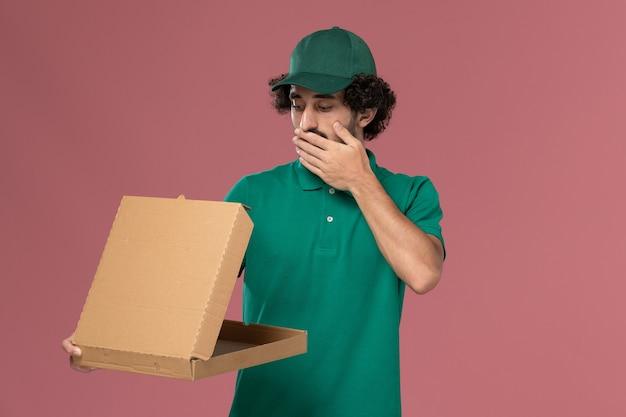 Vue avant de courrier masculin en uniforme vert et cape tenant la boîte de nourriture de livraison sur le fond rose clair de la livraison uniforme des ouvriers de service