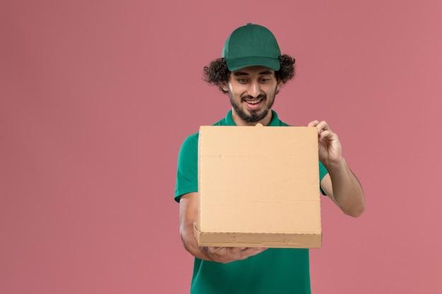 Vue avant de courrier masculin en uniforme vert et cape tenant la boîte de nourriture de livraison de l'ouvrir sur fond rose service de livraison uniforme