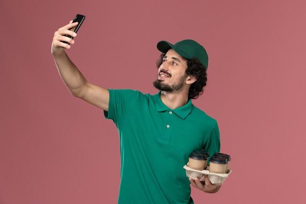 Vue avant de courrier masculin en uniforme vert et cape tenant des tasses à café en prenant photo sur fond rose service de livraison uniforme de travail de travailleur masculin