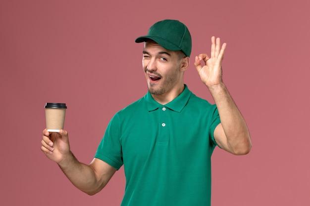 Vue avant de courrier masculin en uniforme vert clignotant et tenant une tasse de café sur le fond rose