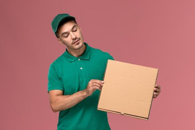 Vue avant de courrier masculin en uniforme vert tenant la boîte de nourriture sur le bureau rose