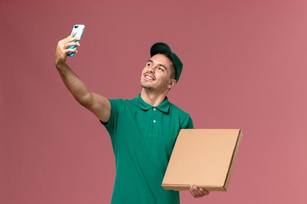 Vue avant de courrier masculin en uniforme vert tenant la boîte de nourriture en prenant une photo avec elle sur fond rose