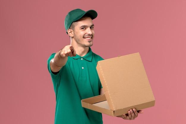 Vue avant de courrier masculin en uniforme vert tenant et ouvrant la boîte de nourriture sur le fond rose clair